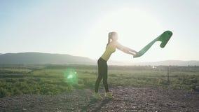 O jovem ostenta a mulher que faz o exercício da ioga - abrir sua esteira verde da ioga em exterior na montanha A menina no sports video estoque