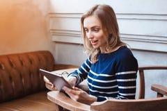 O jovem que smaling o estudante fêmea está conversando na almofada da tabuleta com amigo ao sentar-se no café moderno, Caucasian  Imagem de Stock