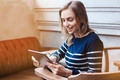 O jovem que smaling o estudante fêmea está conversando na almofada da tabuleta com amigo ao sentar-se no café moderno, Caucasian  Fotos de Stock