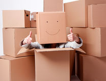 O.k. woman with smiling cardboard boxes on head Stock Images