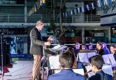 O kapellmeister dirige o desempenho da banda filarmônica da cidade na fase na frente da municipalidade em honra do 70th annive Fotografia de Stock