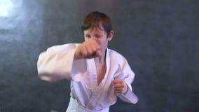 O karaté do adolescente na luta do quimono entrega aos punhos de ondulação o movimento lento vídeos de arquivo