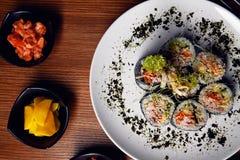 O kimbap dos rolos de sushi ou o corte coreano do gimbap serviram em uma placa imagem de stock