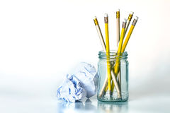 o lápis amarelo dourado no frasco de vidro com papel amarrotado sobre Imagem de Stock Royalty Free