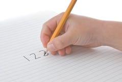 O lápis da terra arrendada da mão da criança, escrita numera no papel Fotografia de Stock