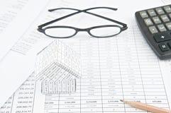 O lápis e a casa na finança explicam com espetáculos e calculadora Foto de Stock Royalty Free