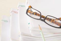 O lápis e os espetáculos puseram sobre a pilha de papel da sobrecarga Fotos de Stock