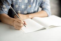 O lápis escreve no caderno foto de stock