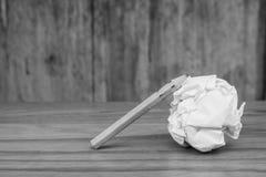 O lápis usado com branco amarrotou a bola de papel posta sobre o assoalho de madeira na imagem preto e branco imagens de stock