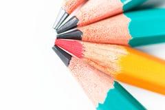 O lápis vermelho entre outro escreve um conceito no fundo branco Foto de Stock