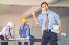 O líder da equipa está seguro na construção Há um fundo imagens de stock