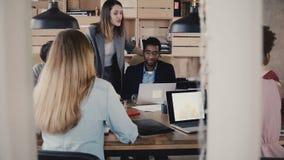 O líder da equipa da mulher vem acima, dá instruções aos colegas na reunião multi-étnico da equipe do negócio no escritório moder video estoque