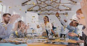O líder da equipe fêmea afro-americano feliz comemora o sucesso comercial com confetes, movimento lento da equipe multi-étnico vídeos de arquivo