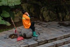 O líquido de limpeza exterior da mulher asiática tem uma ruptura para uma conversa telefônica foto de stock royalty free