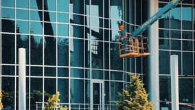 O líquido de limpeza de vidro do homem de funcionamento em um elevador hidráulico lava janelas na construção do arranha-céus do c filme