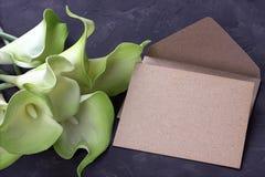 O lírio de calla verde e amarelo floresce com o envelope no fundo do cinza do emplastro Copie o espaço foto de stock