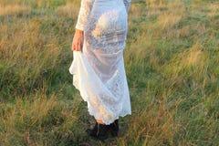 O laço branco do vestido da mulher modela o por do sol exterior da natureza Imagens de Stock