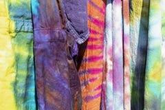 O laço brilhantemente colorido do boho tingiu os vestuários que penduram junto - fundo - o foco seletivo fotografia de stock