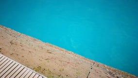 O lado de uma associação, borda de pedra do travertino, lavada por ondas pequenas da água de turquesa iluminou-se pelo sol filme