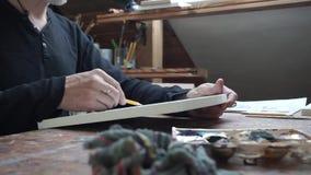 O lado disparou das mãos do artista masculino, tirando o esboço no papel em seu estúdio video estoque