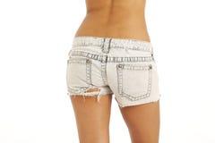 O lado traseiro do brim desgastando da mulher nova shorts Foto de Stock