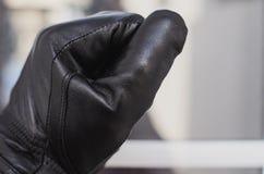 O ladrão, luvas pretas vestindo, bate na janela da casa para verificar se os proprietários são em casa fotografia de stock royalty free