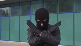 O ladrão ou o ladrão criminoso do homem na máscara estão mostrando o gesto do sinal da parada cruzando suas mãos video estoque
