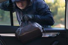 O ladrão rouba um saco do carro através do vidro aberto imagens de stock