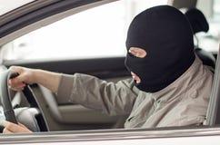 O ladrão na máscara rouba o carro Imagens de Stock