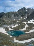 O lago congelado entre as montanhas que aumentam em torno dele fotografia de stock royalty free