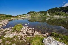 O lago fish e a cabana da montanha, os sete lagos Rila, montanha de Rila Foto de Stock