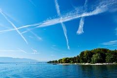 O lago Genebra com muitos jato do avião arrasta no céu Fotografia de Stock Royalty Free
