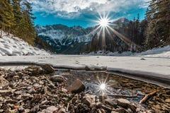 O lago maravilhoso Eibsee Eibsee em Baviera, Alemanha, com gelo e neve - a montanha Zugspitze está na parte traseira com nuvens e imagens de stock