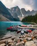 O lago moraine e o caiaque do barco canoe com as montanhas do parque nacional de Banff em Canadá foto de stock