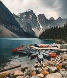 O lago moraine e o caiaque do barco canoe com as montanhas do parque nacional de Banff em Canadá imagens de stock royalty free