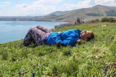 O lago Sevan ? o corpo de ?gua o maior em Arm?nia e na regi?o de C?ucaso Extens?es azuis da ?gua, montanhas, um prado com fl foto de stock