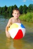 O lago um rapaz pequeno que joga com uma bola inflável Foto de Stock