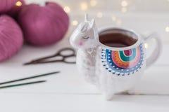 O lama colorido deu forma à caneca do chá ou de café com agulhas de confecção de malhas, tesouras e fio de lãs foto de stock