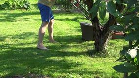 O landscaper masculino sega a grama entre flores e árvores de fruto na jarda do jardim 4K filme
