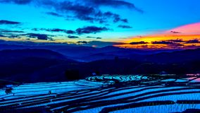 O lapso de tempo, céu após o por do sol sobre os campos do arroz refletiu na água filme