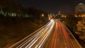 O lapso de tempo do sinal arrasta na autoestrada de um estado a outro de 84 Banfield com skyline da cidade de Portland na cidade