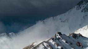 O lapso de tempo, nuvens roda através das montanhas do inverno cobertas com a neve filme