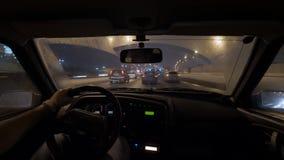 O lapso do movimento disparado do motorista masculino está sentando-se guardando o volante no carro, montando na cidade da noite vídeos de arquivo