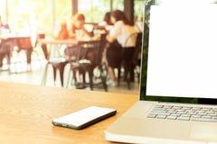 O laptop e o telefone celular na tabela de madeira com imagem de borrão de studen no fundo fotografia de stock royalty free