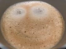 O latte do cappuccino do café da manhã com a cara feliz bem-vinda de sorriso da espuma ou do chocolate tem um dia agradável Imagens de Stock