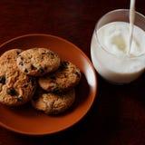 O leite é derramado em um vidro Cookies de farinha de aveia em uma placa Fotos de Stock Royalty Free