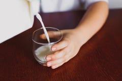 O leite é derramado em uma caneca Imagem de Stock Royalty Free