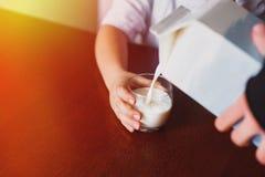 O leite é derramado em uma caneca Fotos de Stock Royalty Free
