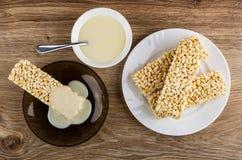 O leite condensado derramou em arrozes tufados nos pires, bacia com leite condensado, arroz tufado na placa na tabela Vista super imagem de stock