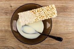 O leite condensado derramou nos arrozes tufados, colher em uns pires marrons na tabela de madeira Vista superior imagem de stock royalty free